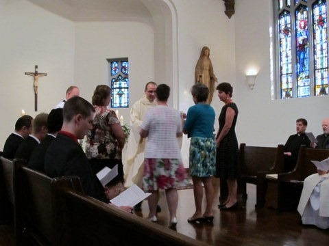 The four moms presenting the gifts to Fr. Andrews.