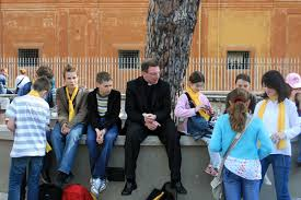 priest and school children