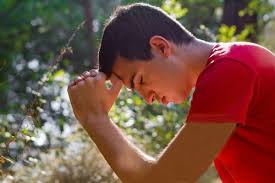 young man praying in nature